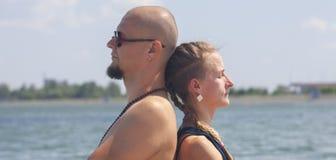 Το άτομο και η έγκυος γυναίκα κάνουν τη γιόγκα στην παραλία στοκ εικόνα με δικαίωμα ελεύθερης χρήσης
