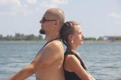 Το άτομο και η έγκυος γυναίκα κάνουν τη γιόγκα στην παραλία στοκ φωτογραφίες