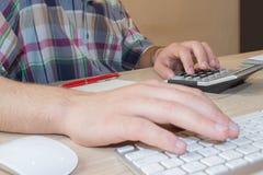 Το άτομο και ο υπολογιστής χρησιμοποιούν έναν υπολογιστή στον πίνακα στο δωμάτιο γραφείων Το άτομο κάθεται στον πίνακα με έναν υπ Στοκ Εικόνα