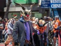 Το άτομο και το παιδί που φορούν τις μάσκες diablo και που κρατούν κτυπούν το Μάρτιο στο α στοκ εικόνες