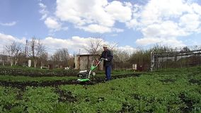 Το άτομο καλλιεργεί το έδαφος στον κήπο με ένα πηδάλιο, που προετοιμάζει το χώμα για τη σπορά φιλμ μικρού μήκους