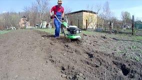 Το άτομο καλλιεργεί το έδαφος στον κήπο με ένα πηδάλιο, που προετοιμάζει το χώμα για τη σπορά απόθεμα βίντεο