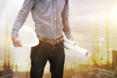 Το άτομο κατασκευαστών που κρατά το άσπρα κράνος και το σχεδιάγραμμα Στοκ εικόνες με δικαίωμα ελεύθερης χρήσης