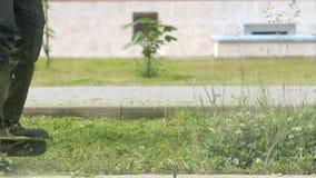 Το άτομο κηπουρών κόβει τη χλόη για να κάνει το όμορφο σχέδιο απόθεμα βίντεο