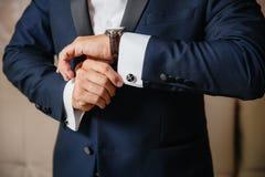 Το άτομο κινηματογραφήσεων σε πρώτο πλάνο βάζει σε ένα χρυσό ρολόι με μια ζώνη δέρματος, ο επιχειρηματίας είναι ντυμένος σε ένα μ στοκ εικόνες