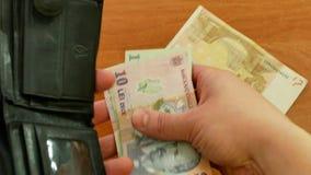 Το άτομο κινηματογραφήσεων σε πρώτο πλάνο παίρνει έξω ρουμανικό Lei από το πορτοφόλι απόθεμα βίντεο