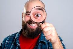 Το άτομο κοιτάζει μέσω της ενίσχυσης - γυαλί Στοκ Εικόνες