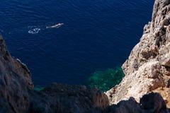 Το άτομο κολυμπά στη σκούρο μπλε θάλασσα στοκ εικόνα