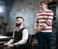 Το άτομο κομμωτών ξυρίζει έναν πελάτη με μια γενειάδα σε ένα barbershop Στοκ Φωτογραφίες