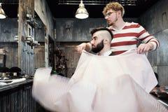 Το άτομο κομμωτών ξυρίζει έναν πελάτη με μια γενειάδα σε ένα barbershop Στοκ Εικόνα