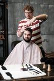 Το άτομο κομμωτών ξυρίζει έναν πελάτη με μια γενειάδα σε ένα barbershop Στοκ εικόνα με δικαίωμα ελεύθερης χρήσης