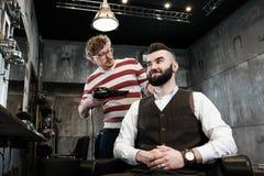 Το άτομο κομμωτών ξυρίζει έναν πελάτη με μια γενειάδα σε ένα barbershop Στοκ φωτογραφία με δικαίωμα ελεύθερης χρήσης