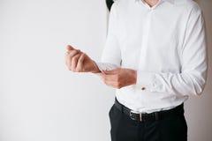 Το άτομο κουμπώνει το μανικετόκουμπο στο γαλλικό άσπρο πουκάμισο πολυτέλειας μανικιών μανσετών στοκ εικόνα