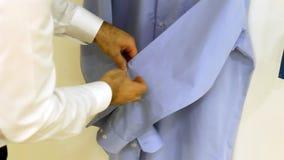 Το άτομο κουμπώνει το πουκάμισο φιλμ μικρού μήκους