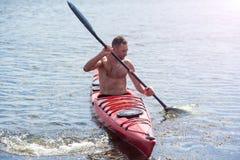Το άτομο κολυμπά σε ένα κόκκινο καγιάκ 02 Στοκ Φωτογραφία