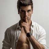 Το άτομο κρατά ένα δάχτυλο στα χείλια του με ένα ανοικτό πουκάμισο στοκ φωτογραφίες με δικαίωμα ελεύθερης χρήσης