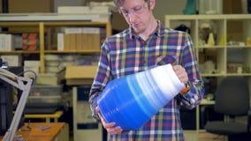 Το άτομο κρατά ένα βάζο γίνοντα στον τρισδιάστατο εκτυπωτή 4K απόθεμα βίντεο
