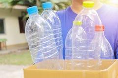 Το άτομο κρατά ένα κιβώτιο εγγράφου με ένα πλαστικό μπουκάλι Για να εμφιαλώσει το προϊόν στοκ φωτογραφίες με δικαίωμα ελεύθερης χρήσης