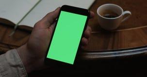Το άτομο κρατά ένα σύγχρονο smartphone με την πράσινη επίδειξη οθόνης σε έναν καφέ με ένα φλιτζάνι του καφέ στον πίνακα απόθεμα βίντεο