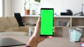 Το άτομο κρατά ένα σύγχρονο smartphone με την πράσινη χλεύη χρώματος οθόνης επάνω φιλμ μικρού μήκους