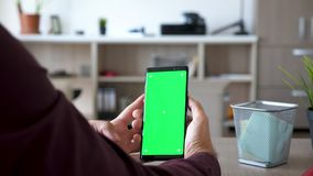 Το άτομο κρατά ένα smarpthone με την πράσινη χλεύη χρώματος οθόνης επάνω απόθεμα βίντεο