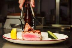 Το άτομο κρατά από τη μέση σπάνια μπριζόλα βόειου κρέατος λαβίδων στο πιάτο Στοκ εικόνα με δικαίωμα ελεύθερης χρήσης