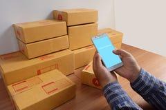 Το άτομο κρατά το κινητό κιβώτιο τηλεφώνων και προϊόντων, στο ξύλινο πάτωμα, ψωνίζοντας on-line στοκ εικόνες με δικαίωμα ελεύθερης χρήσης