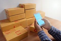 Το άτομο κρατά το κινητό κιβώτιο τηλεφώνων και προϊόντων, στο ξύλινο πάτωμα, ψωνίζοντας on-line στοκ φωτογραφία με δικαίωμα ελεύθερης χρήσης
