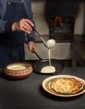 Το άτομο κρατά μια κουτάλα και χύνει τη ζύμη στο τηγάνι στοκ εικόνα