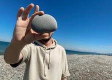 Το άτομο κρατά μια πέτρα μπροστά από το πρόσωπό του Μια θέση για μια ετικέτα στοκ φωτογραφίες