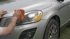 Το άτομο κρατά προβολείς hatchback πλυσιμάτων σφουγγαριών τους προσεκτικά γκρίζους απόθεμα βίντεο