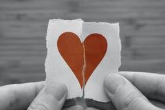 Το άτομο κρατά την κόκκινη σπασμένη καρδιά εγγράφου στα χέρια του Στοκ Εικόνες