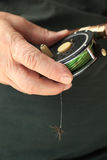Το άτομο κρατά το εξέλικτρο αλιείας μυγών και την τεχνητή μύγα Στοκ εικόνες με δικαίωμα ελεύθερης χρήσης