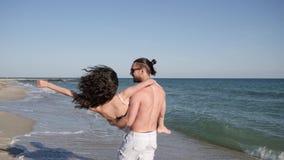 Το άτομο κρατά το κορίτσι στα όπλα στην παραλία, νέοι που περπατά χωρίς παπούτσια στην άμμο, συνδέει ερωτευμένος εξωτικές διακοπέ απόθεμα βίντεο