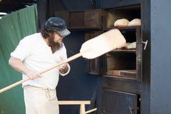 Το άτομο κρατά το φτυάρι σε ένα ψωμί φραντζολών Στοκ εικόνα με δικαίωμα ελεύθερης χρήσης
