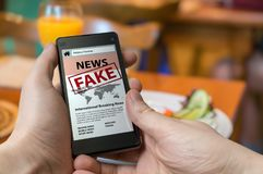 Το άτομο κρατά το smartphone και διαβάζει τις πλαστές ειδήσεις στο διαδίκτυο Έννοια προπαγάνδας, παραπληροφόρησης και εξαπάτησης Στοκ Εικόνα