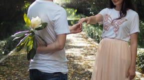Το άτομο κρύβει το άσπρο λουλούδι πίσω από τον προκειμένου να εκπλαγεί η φίλη του στοκ φωτογραφίες