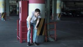 Το άτομο κρύβει πίσω από τη στήλη στον υπόγειο χώρο στάθμευσης με πολλά αυτοκίνητα απόθεμα βίντεο