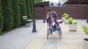 Το άτομο κυλά έναν ευτυχή έφηβο σε μια αναπηρική καρέκλα στο πάρκο απόθεμα βίντεο