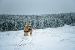 Το άτομο κυνηγών έντυσε στον ιματισμό κάλυψης που στέκεται το χειμώνα Στοκ φωτογραφίες με δικαίωμα ελεύθερης χρήσης