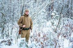Το άτομο κυνηγών έντυσε στον ιματισμό κάλυψης που στέκεται το χειμώνα Στοκ Φωτογραφία