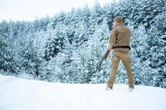 Το άτομο κυνηγών έντυσε στον ιματισμό κάλυψης που στέκεται το χειμώνα Στοκ Φωτογραφίες