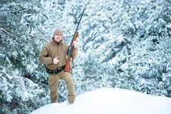 Το άτομο κυνηγών έντυσε στον ιματισμό κάλυψης που στέκεται το χειμώνα Στοκ Εικόνες