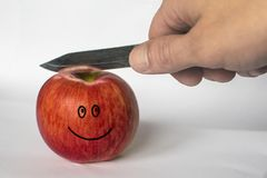 Το άτομο κόβει ένα κόκκινο μήλο με ένα μαχαίρι E στοκ φωτογραφίες