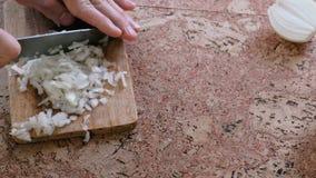 Το άτομο κόβει ήπια το κρεμμύδι στα μικρά κομμάτια Κινηματογράφηση σε πρώτο πλάνο χεριών ατόμων ` s απόθεμα βίντεο