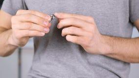 Το άτομο κόβει τα καρφιά του από τους Clippers Χέρια κινηματογραφήσεων σε πρώτο πλάνο Γκρίζα μπλούζα στο υπόβαθρο απόθεμα βίντεο