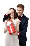 Το άτομο κλείνει τα μάτια της φίλης του για να δώσει ένα παρόν στο κόκκινο κιβώτιο στοκ φωτογραφία με δικαίωμα ελεύθερης χρήσης