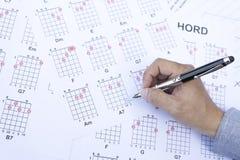 Το άτομο μαθήματος κιθάρων γράφει το διάγραμμα κιθάρων χορδών Στοκ Εικόνες