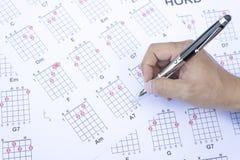 Το άτομο μαθήματος κιθάρων γράφει το διάγραμμα κιθάρων χορδών Στοκ Εικόνα