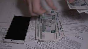 Το άτομο μετρά το ρωσικό ρούβλι χρημάτων πέρα από τον άσπρο πίνακα γιατί οι λογαριασμοί χρησιμότητας πληρώνουν το σε αργή κίνηση  φιλμ μικρού μήκους